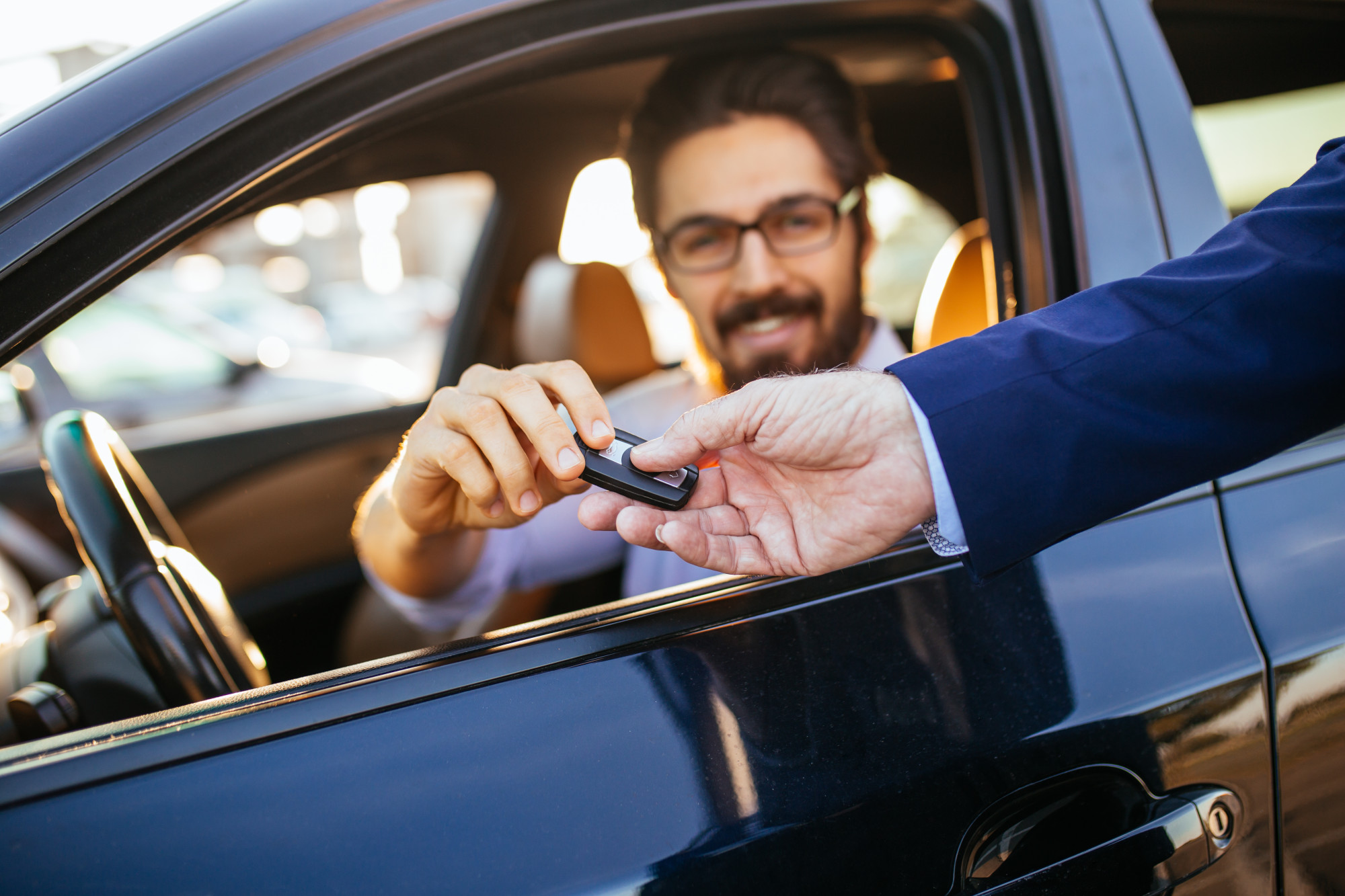 person handing key to driver